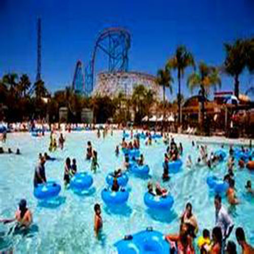 People in the pool at a water park with blue floating tubes with a roller coaster in the background