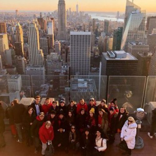Educational Discovery Tours group on rooftop of building with New York city and the sunset in the background