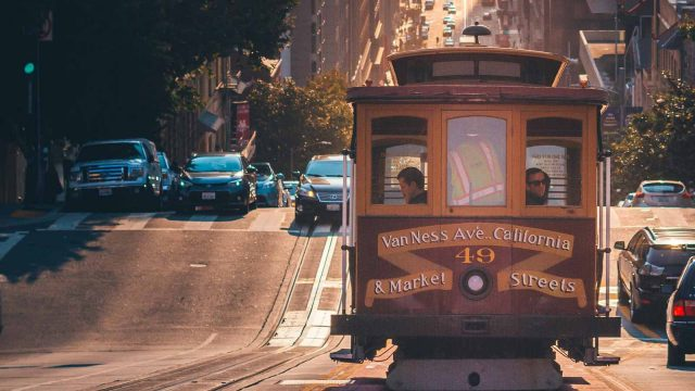 People riding inside a cable car on the busy San Francisco, California roads