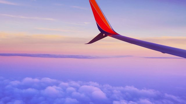 Left wing of an airplane flying through a purple and orange clouded sky